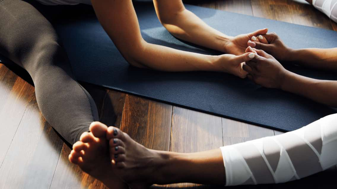 Two woman stretching and holding hands in a yoga class at Life Time.