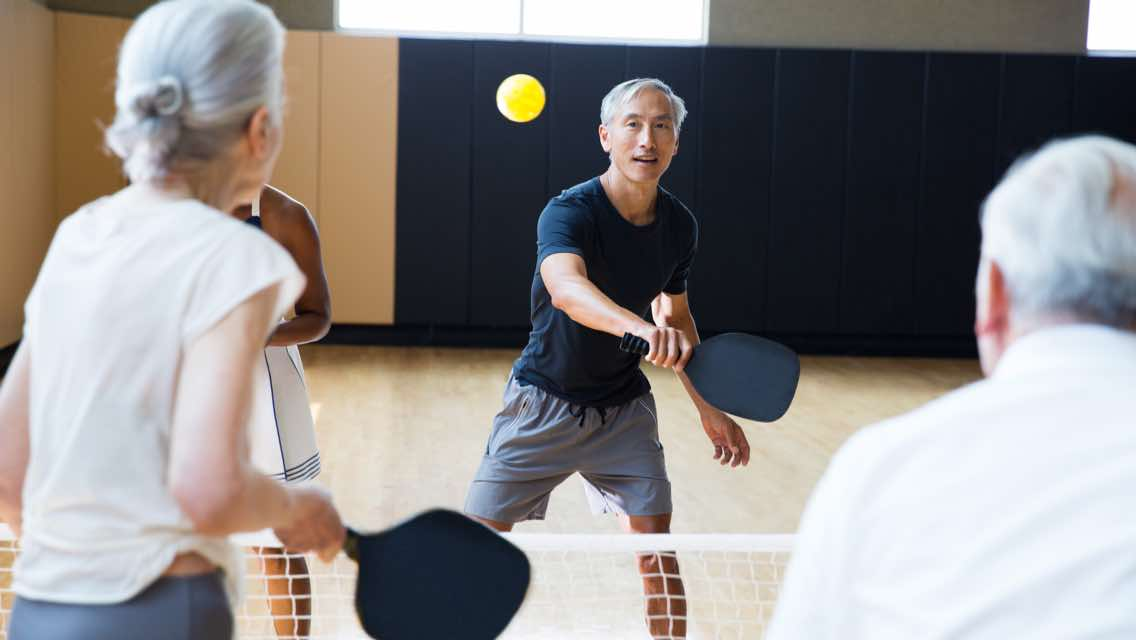 Four people playing pickleball on an indoor court at Life Time