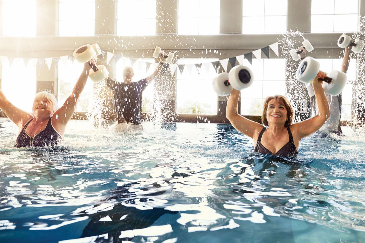 Four people working out in an indoor water aerobics class at Life Time