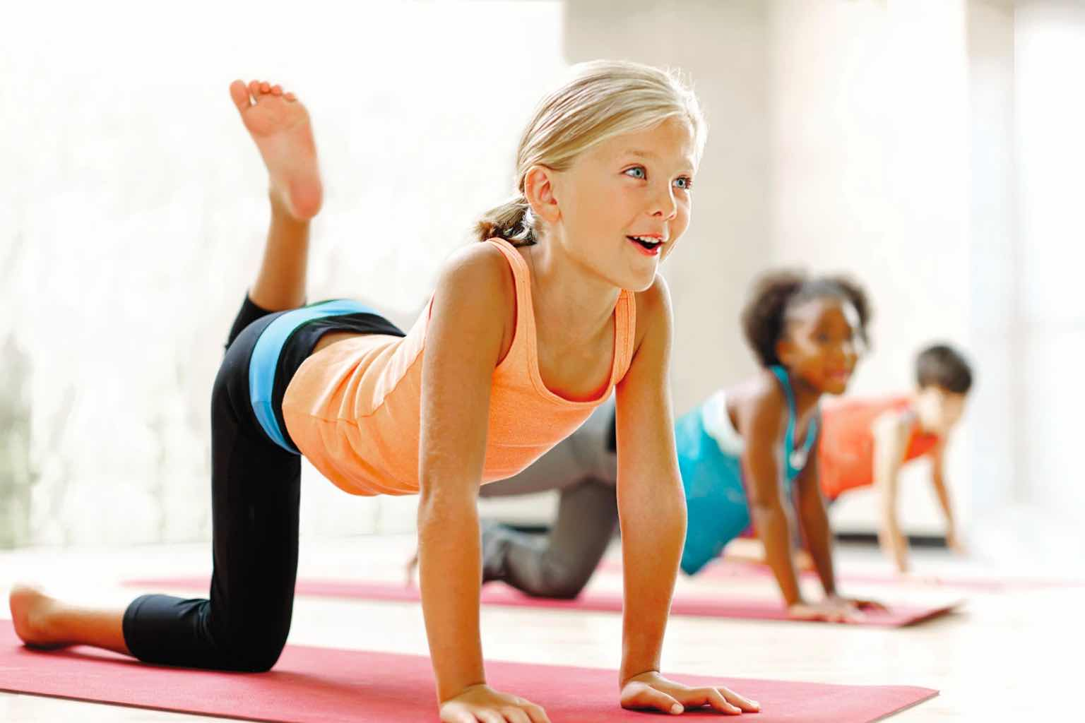 a young girl smiling while doing yoga