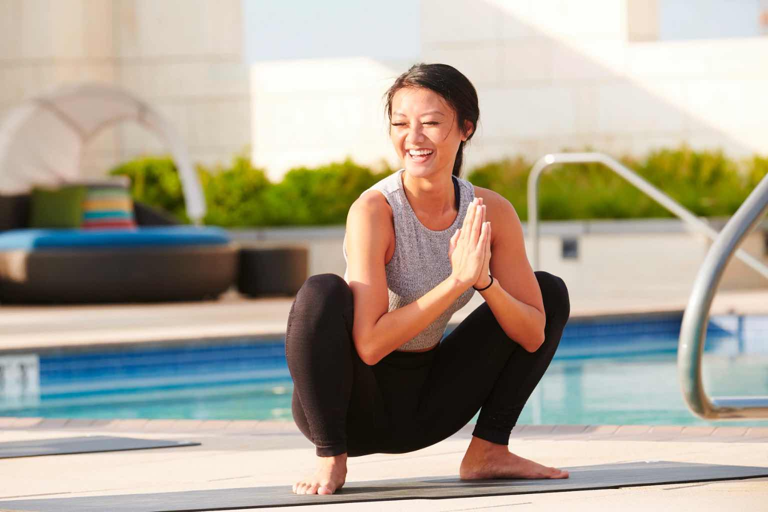 a woman smiling by a pool doing a yoga squat
