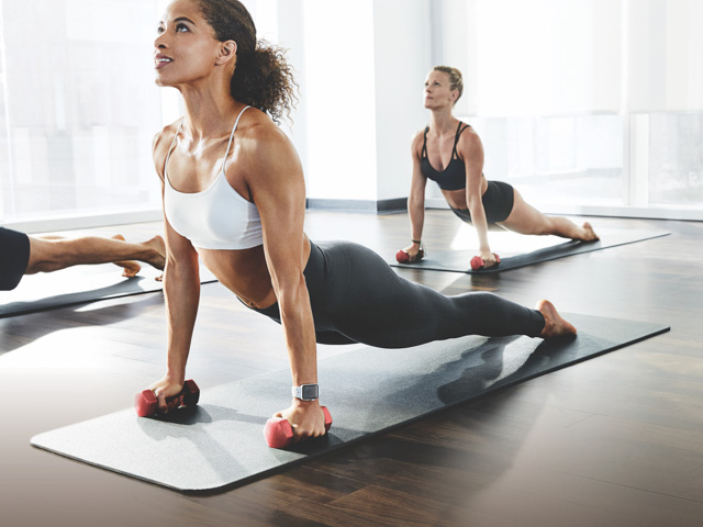 3 people performing a yoga position with handweights in a well lit yoga studio at a Life Time location