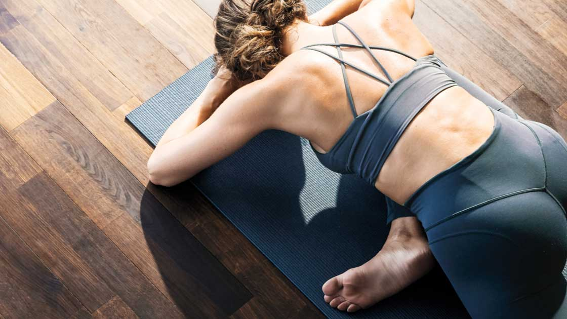 A woman on a yoga mat in a stretching pose