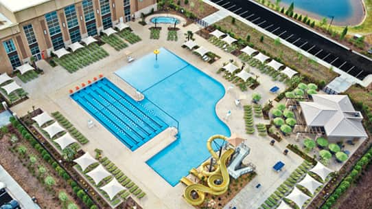 A aerial view of a Life Time outdoor pool with waterslides and lap pool along with lounge chairs