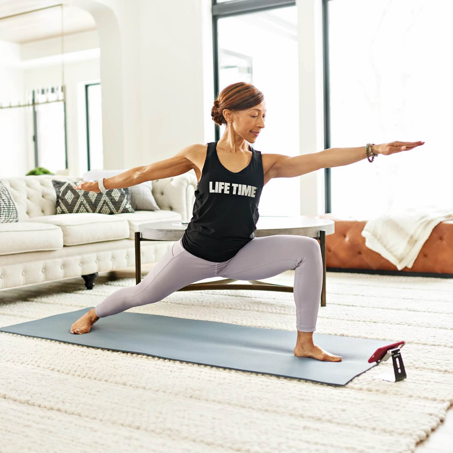 Woman with Life Time tank top does yoga in her living room