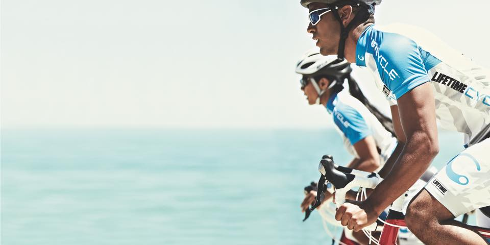 A male and female cycling in Life Time gear with the ocean in the background