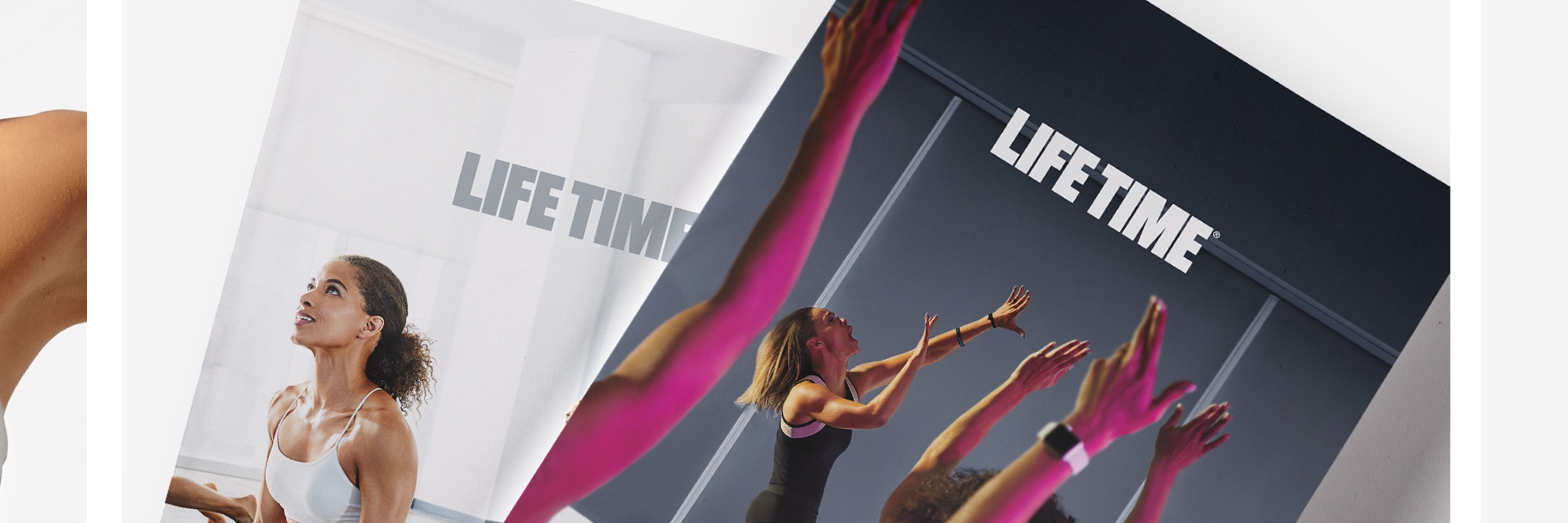 2 Life Time magazines, stacked on top of each other. One showing a women in a yoga pose with the Life Time logo above her, the second shows an indoor cycling class with the life time logo above.