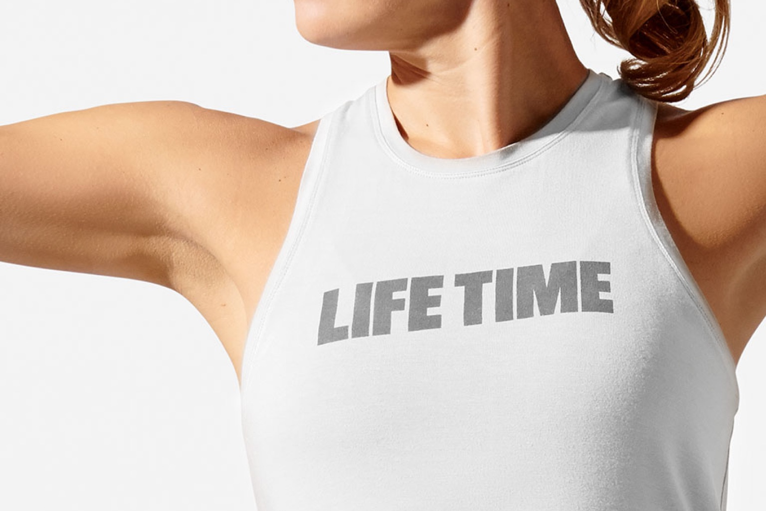 A close view of a grey life time logo on the front of a white tank worn by a woman