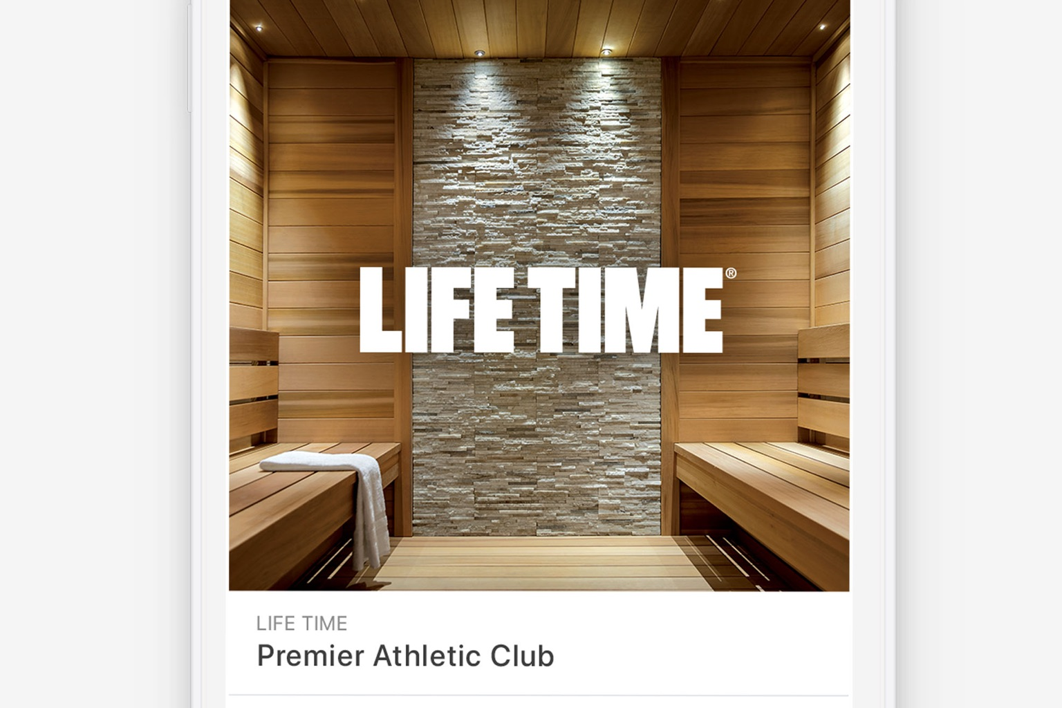 An example of a web page component showing a white Life Time logo over an image of a sauna