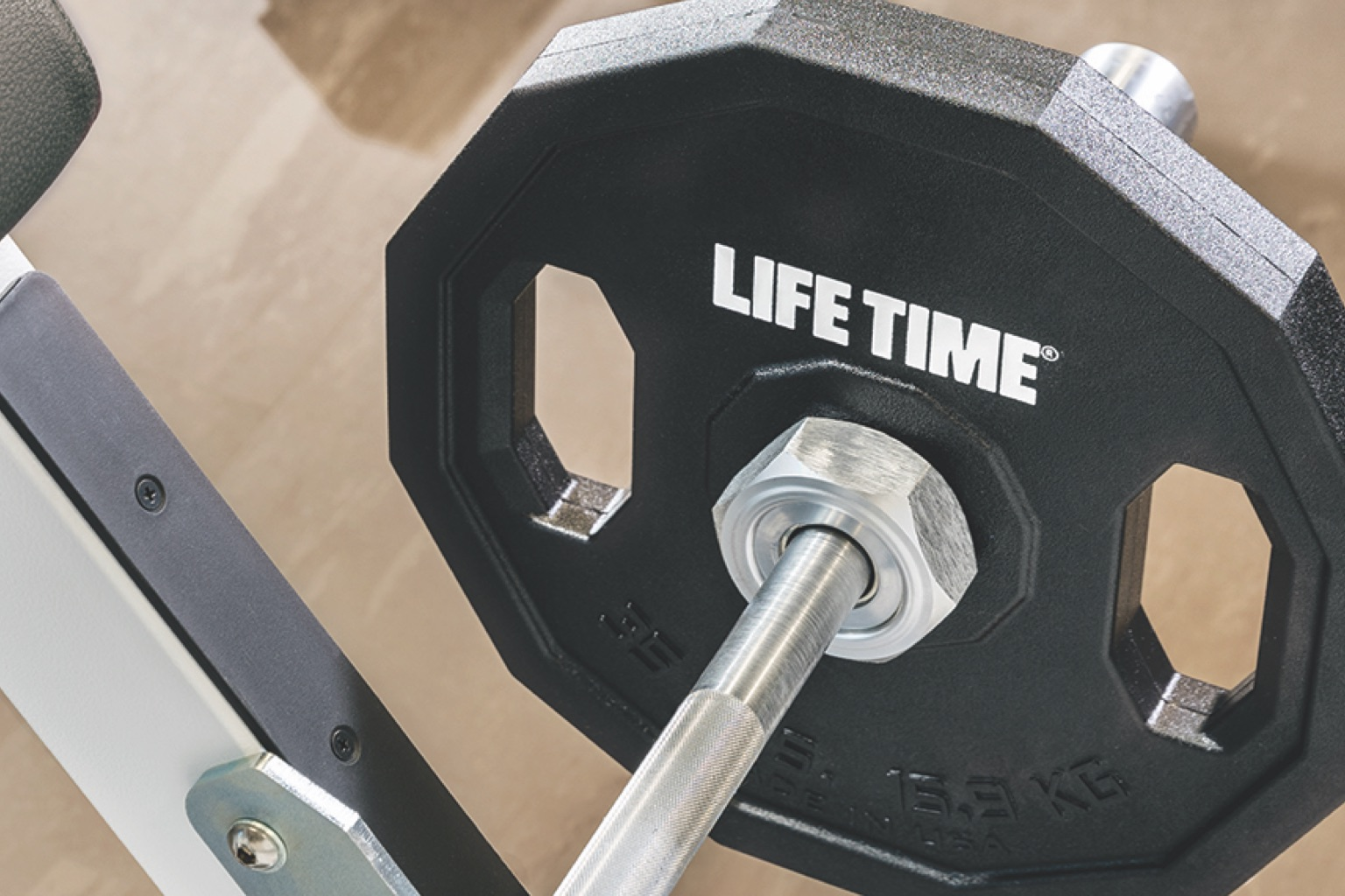A close view of a barbell with a weight that shows a white Life Time logo