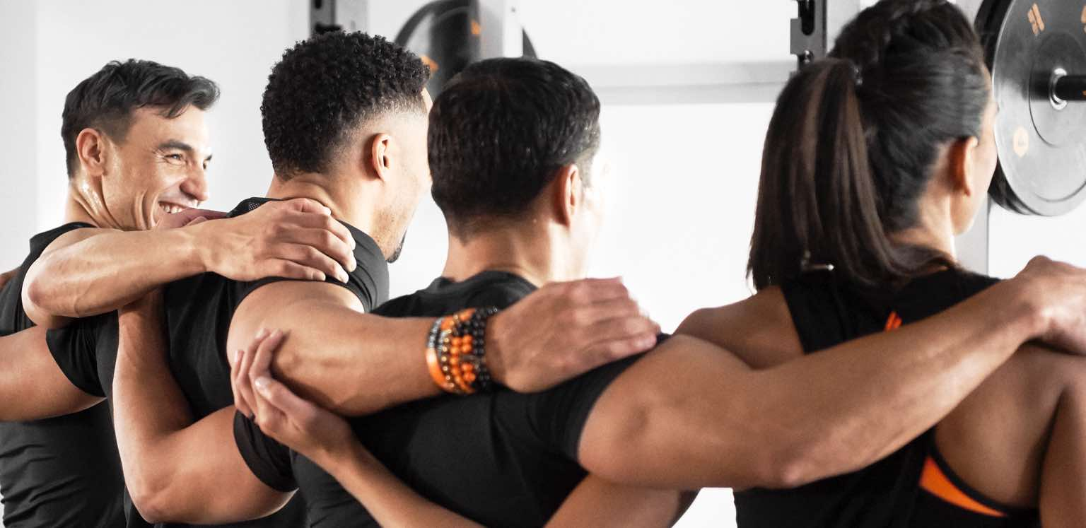 Four people standing with their arms around each other during a group training class at Life Time