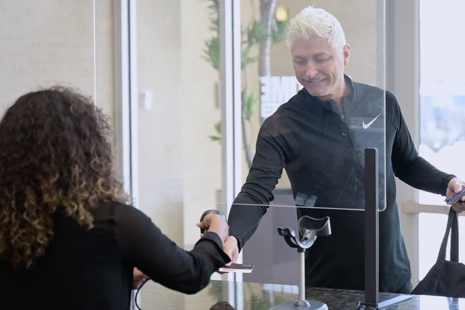 A person checking in at a Life Time Athletic front desk