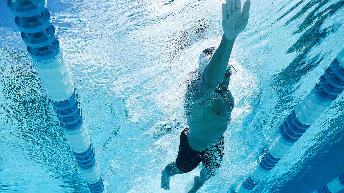 An underwater view of a male swimmer swimming laps