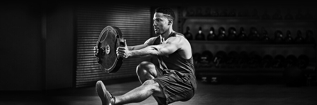 An athletic man in a challenging squat position holding a weight