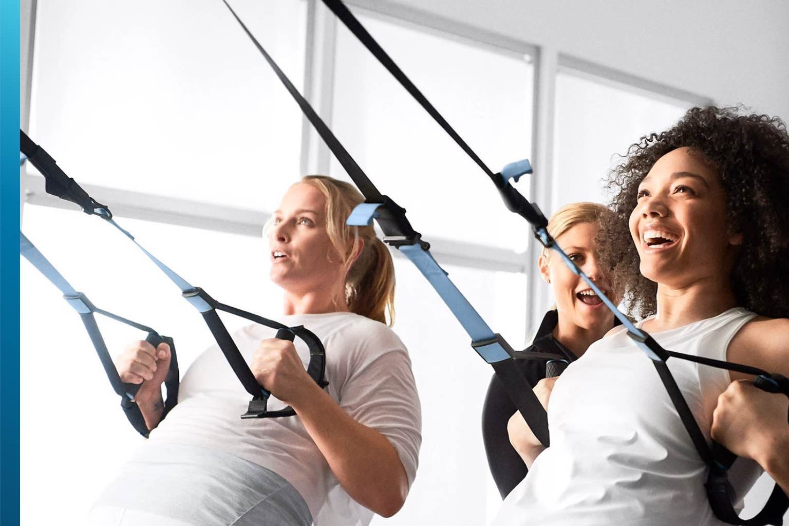 A trainer motivates two women using TRX straps during a group training class at Life Time