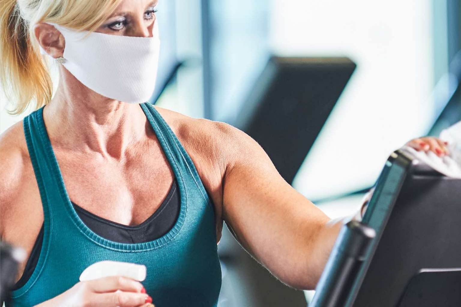 A woman in workout gear and a face mask wipes down her treadmill with disinfectant