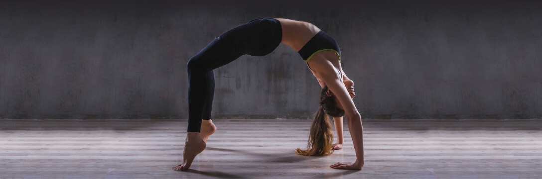 A woman completing a yoga backbend