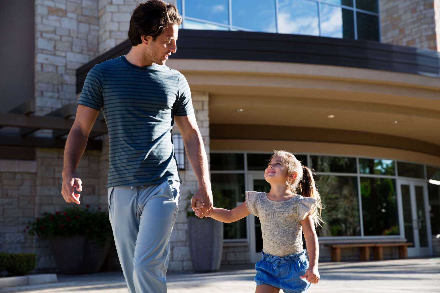 Father and daughter walking outside of a Life Time building.
