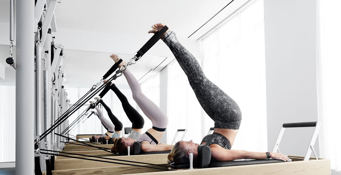 A group of women on Pilates Reformer Machines during a Pilates class