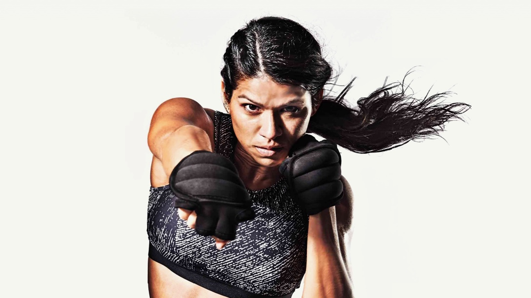 A woman performing a boxing punch while her hair swishes behind her