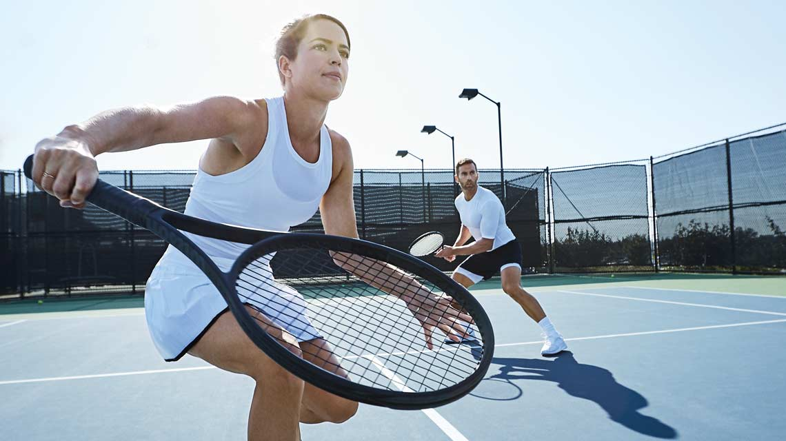 A man and a woman playing doubles tennis on a Life Time Outdoor Tennis Court