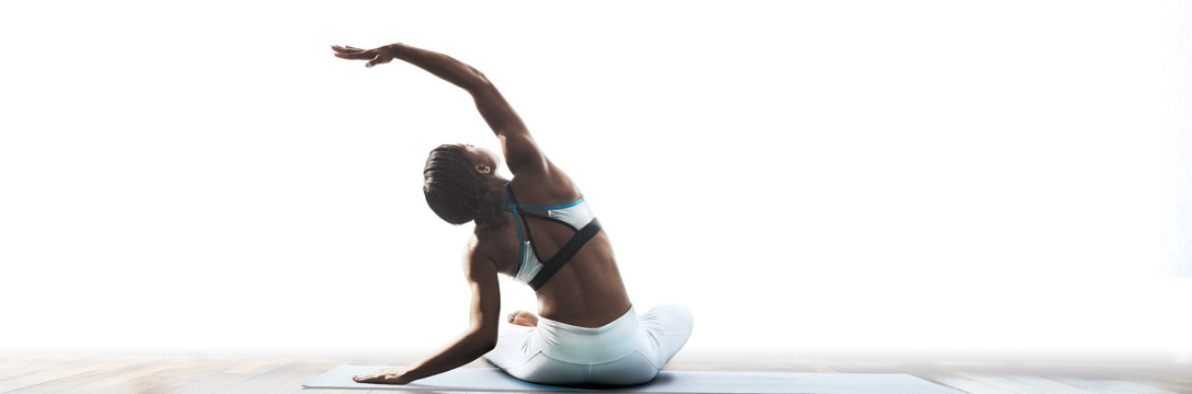 A woman yogi sitting on a mat performing a side bend stretch
