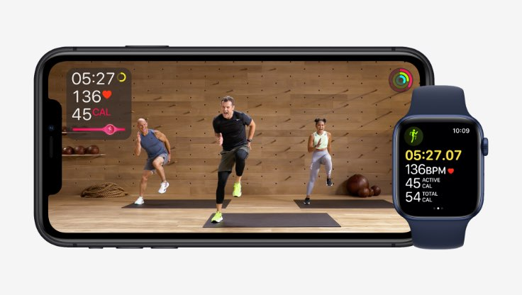 An Apple Watch sits near a phone whose screen displays three people in a fitness class