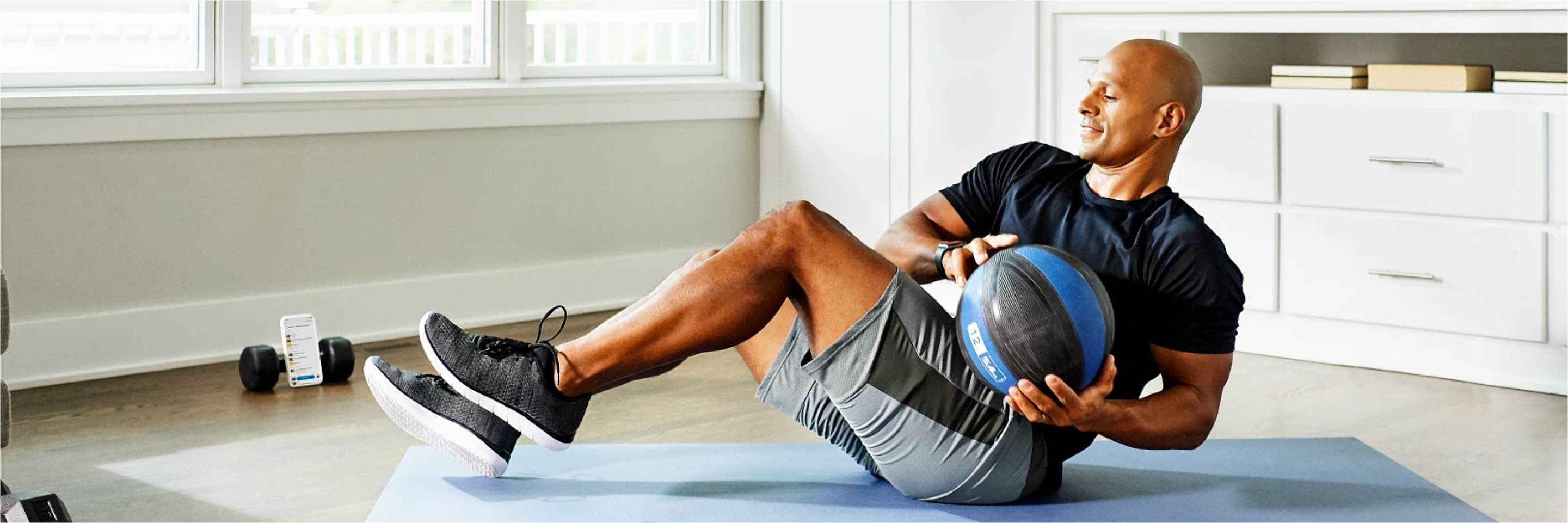 A man completes a medicine ball workout at home