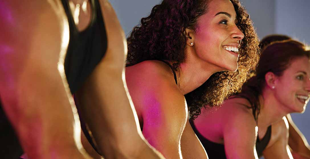 2 women smiling while working out in an indoor cycling class