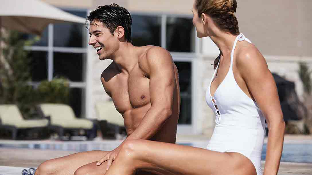 A smiling young man and woman in swimwear sit together on a sunny pool deck