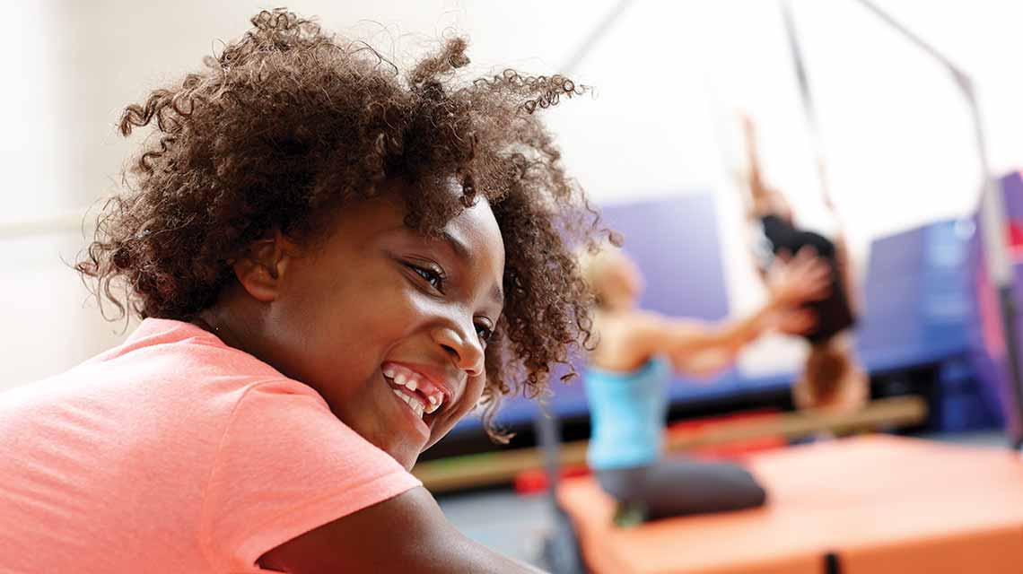 A young girl enjoying gymnastics class