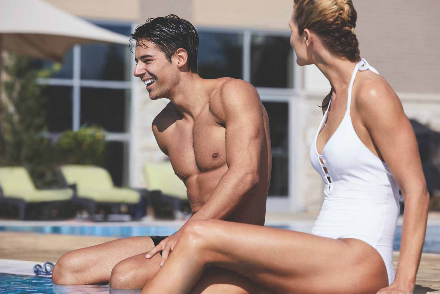 A smiling young woman and man in swimwear sit together on a sunny pool deck