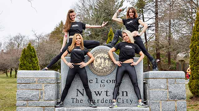 Chestnut Hill Life Time Athletic instructors posing by a city of Newton sign