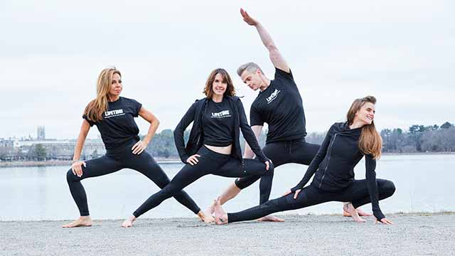 Instructors from Chestnut Hill Life Time Athletic club do yoga poses by the water