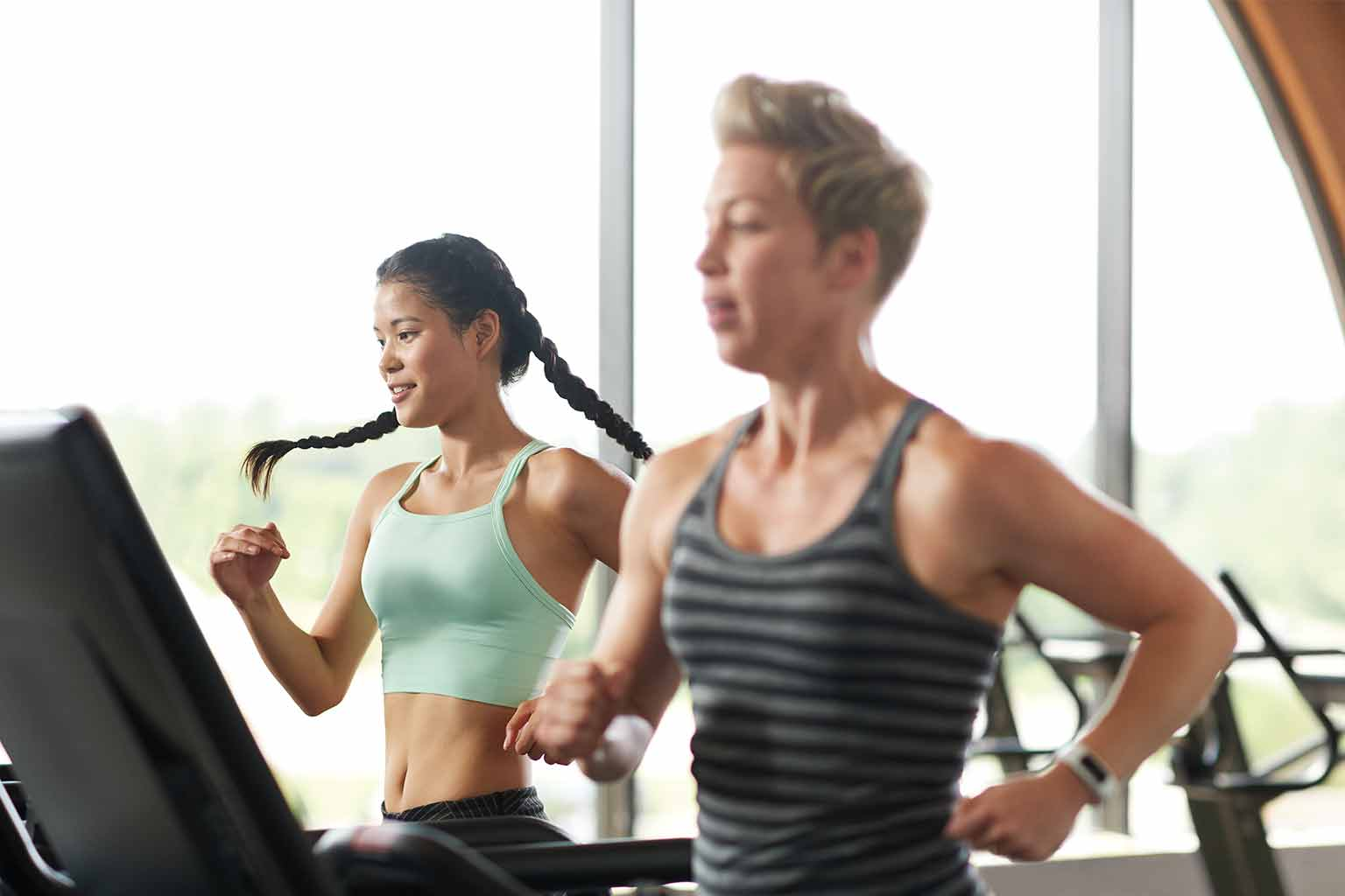 A couple women working out on a treadmil