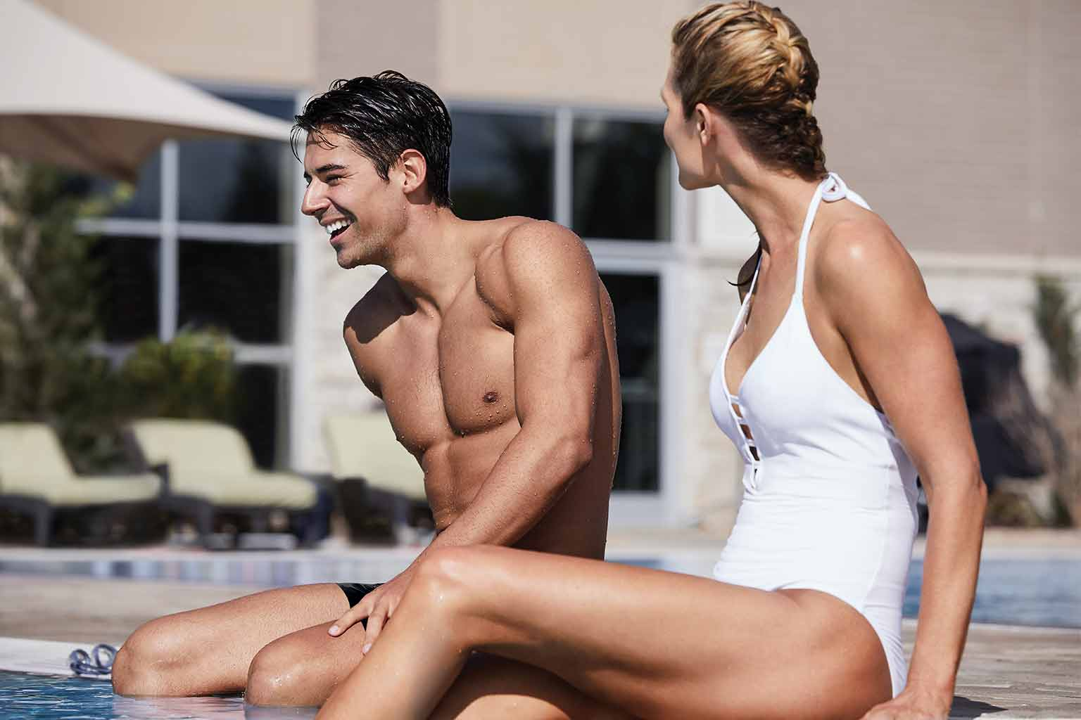 a man and a women laugh while sitting on the edge of an outdoor pool