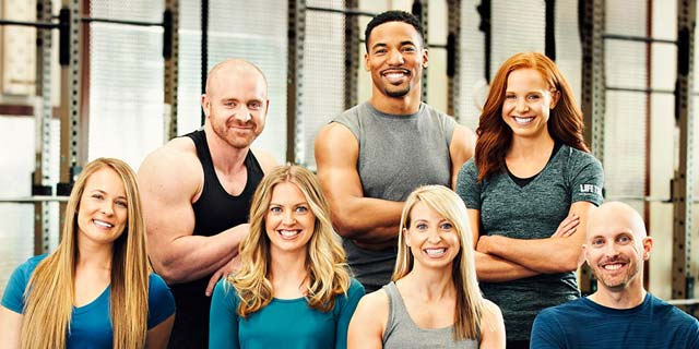 Seven Life Time Trainers and Registered Dietitians on a fitness floor smiling at the camera