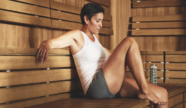 Women in her workout clothes sitting in the sauna