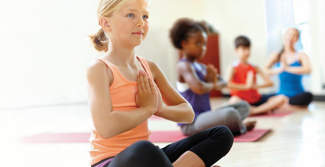 A girl in yoga class sitting with legs crossed and palms together
