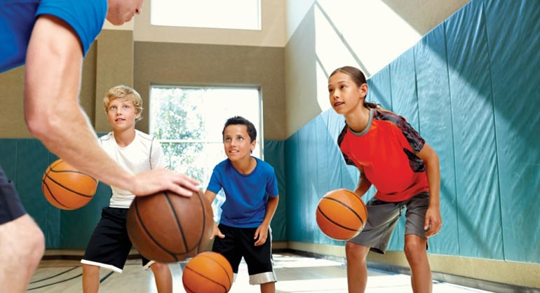 A coach and three young boys dribbling basketballs in a gym