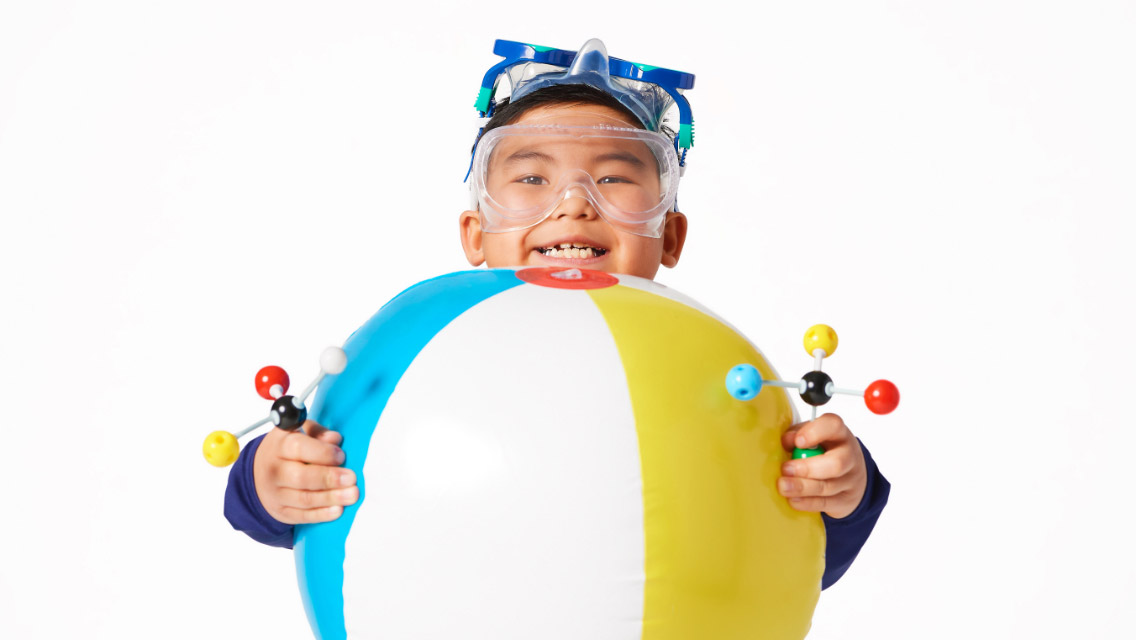 Laughing boy wearing science goggles and holding a beach ball and molecule models