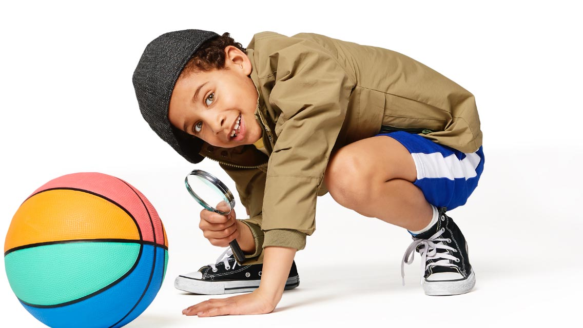 Crouching boy dressed as a detective holding a magnifying glass up to a multi-colored basketball