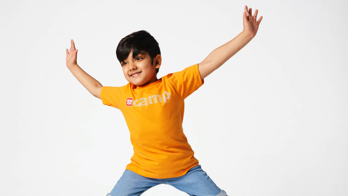 Happy, smiling boy wearing a yellow summer camp t-shirt with arms and legs outstretched as he jumps with joy