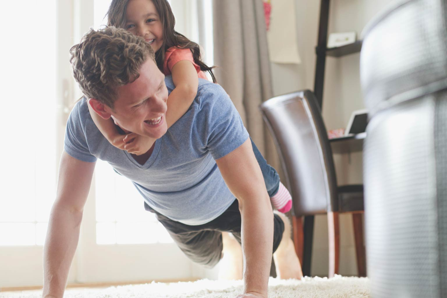 Man doing a pushup with daughter on his back at home