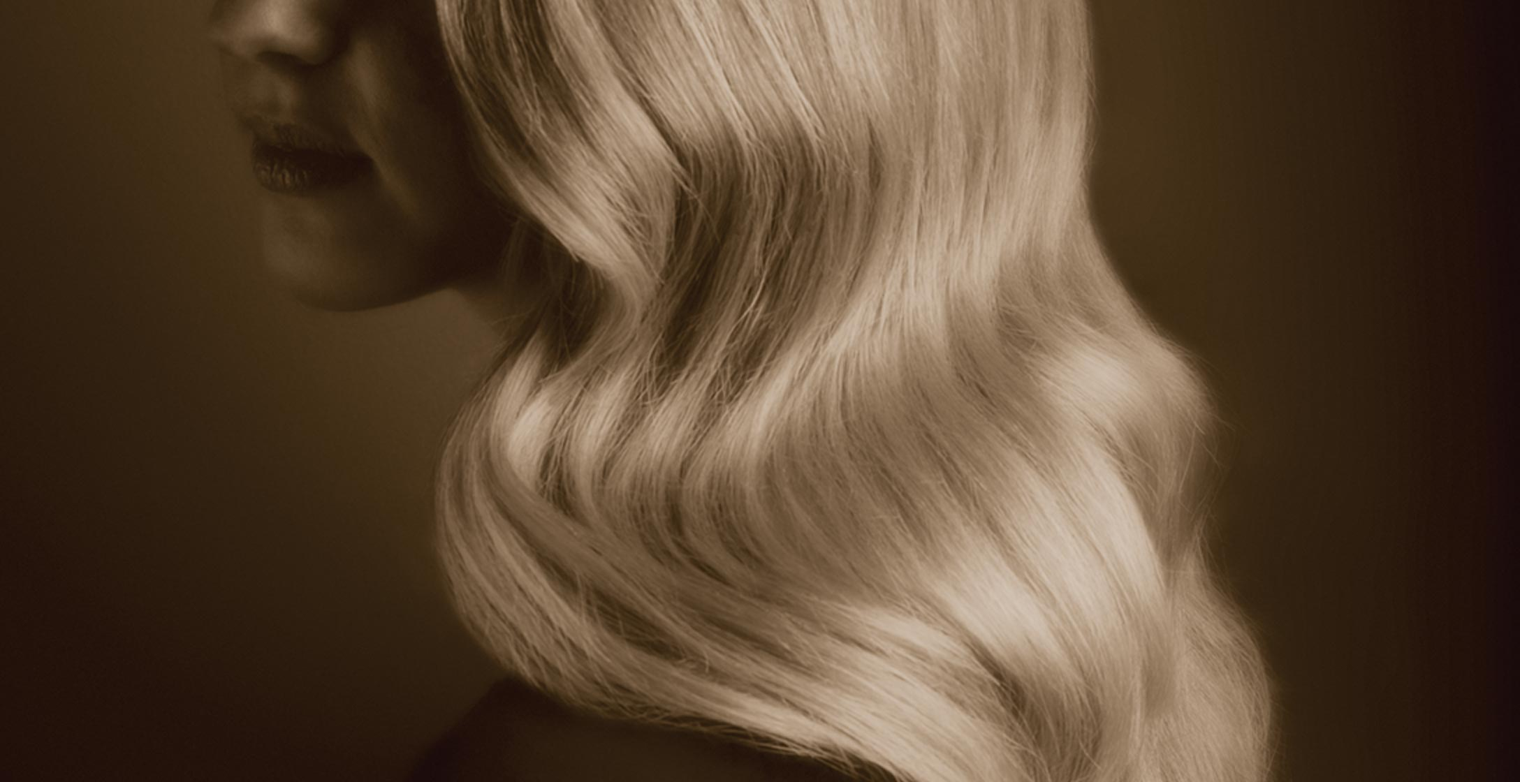A woman's head in profile with long, waved, blond hair