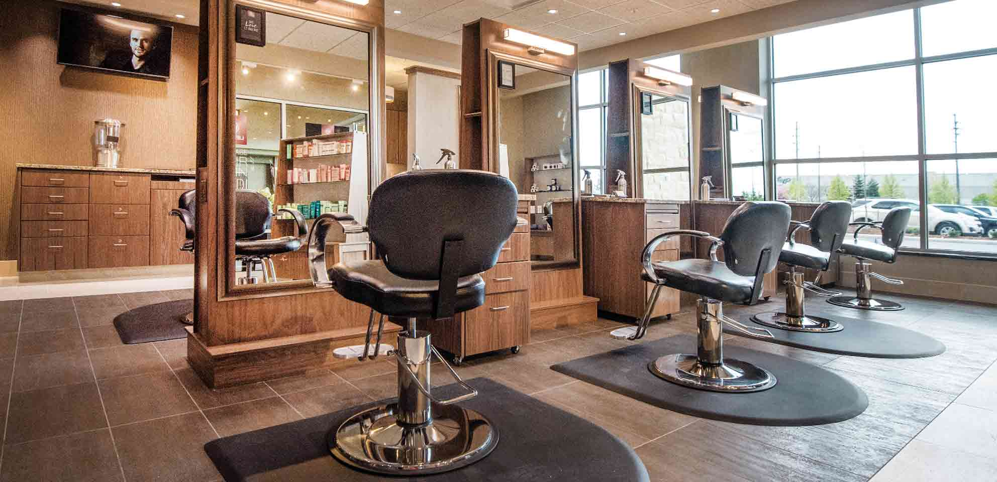 Four hair stylists' chairs and stations in a hair salon