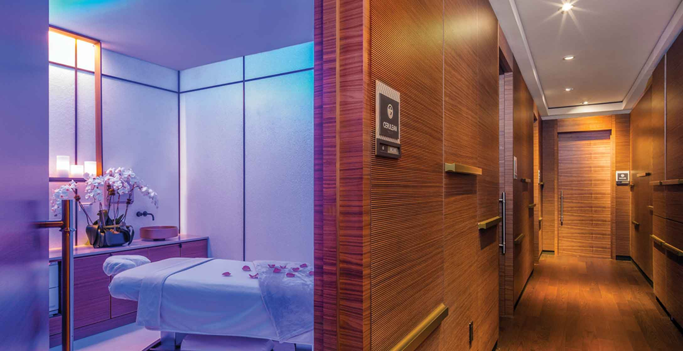 A softly lit massage room off a wood-paneled hallway