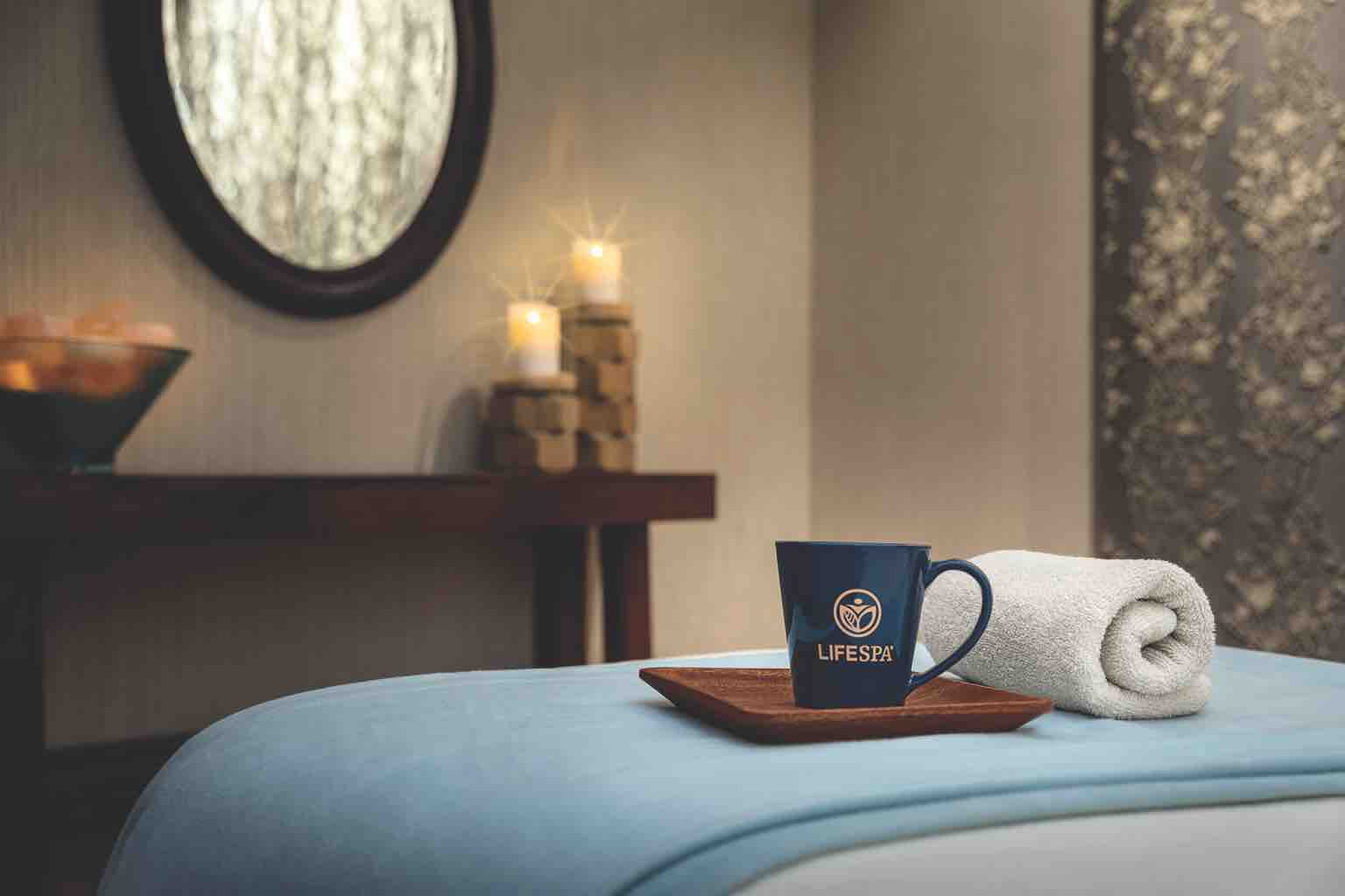 A rolled white towel and a mug with a LifeSpa logo sit atop a blanket-covered massage table