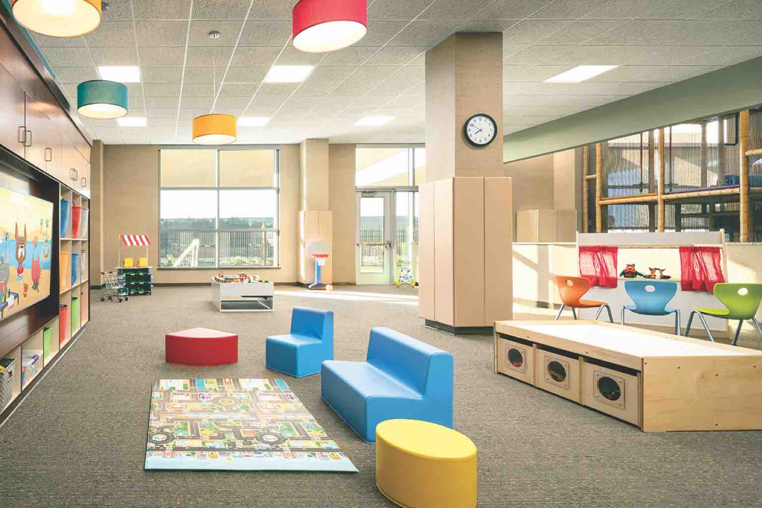 A colorful child center featuring bright cubbies, toys and a video-watching area filled with child-sized furniture