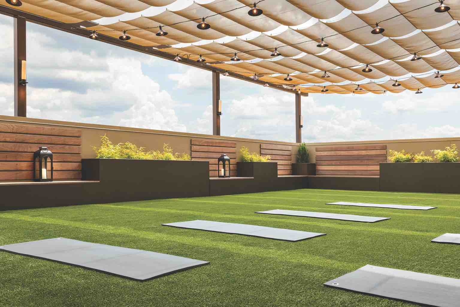 A turf-covered rooftop yoga studio shaded by a pergola and surrounded by wood benches and natural planters